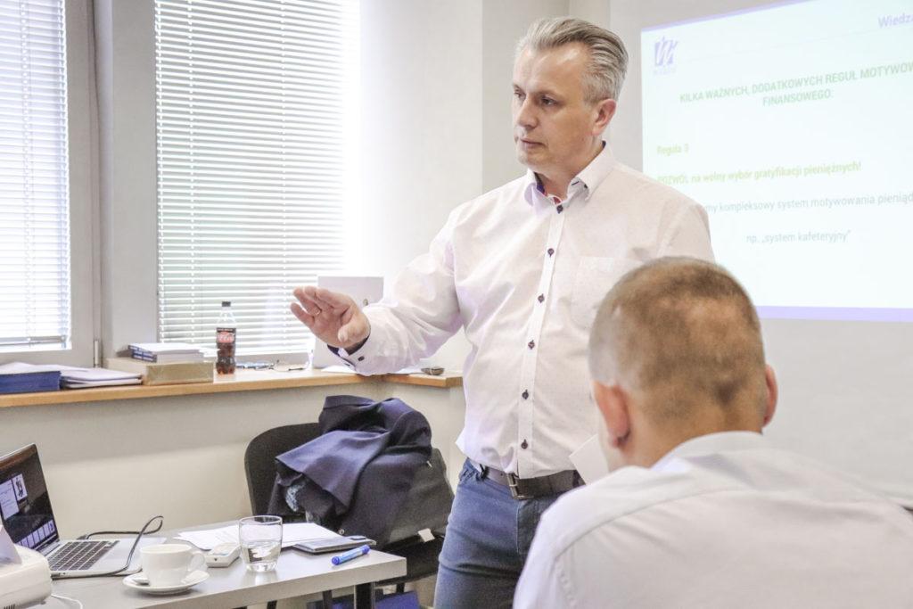 Trener Leszek omawia z grupą kwestie motywowania pracowników metodami pozafinansowymi