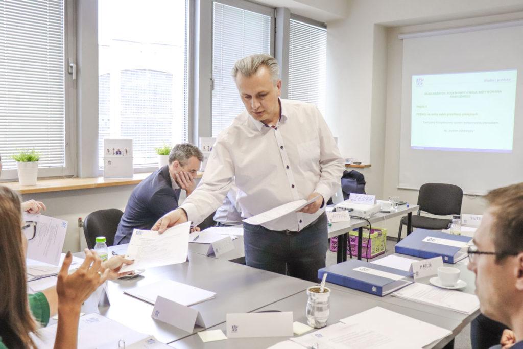 Trener Leszek rozdaje materiały do gry szkoleniowej