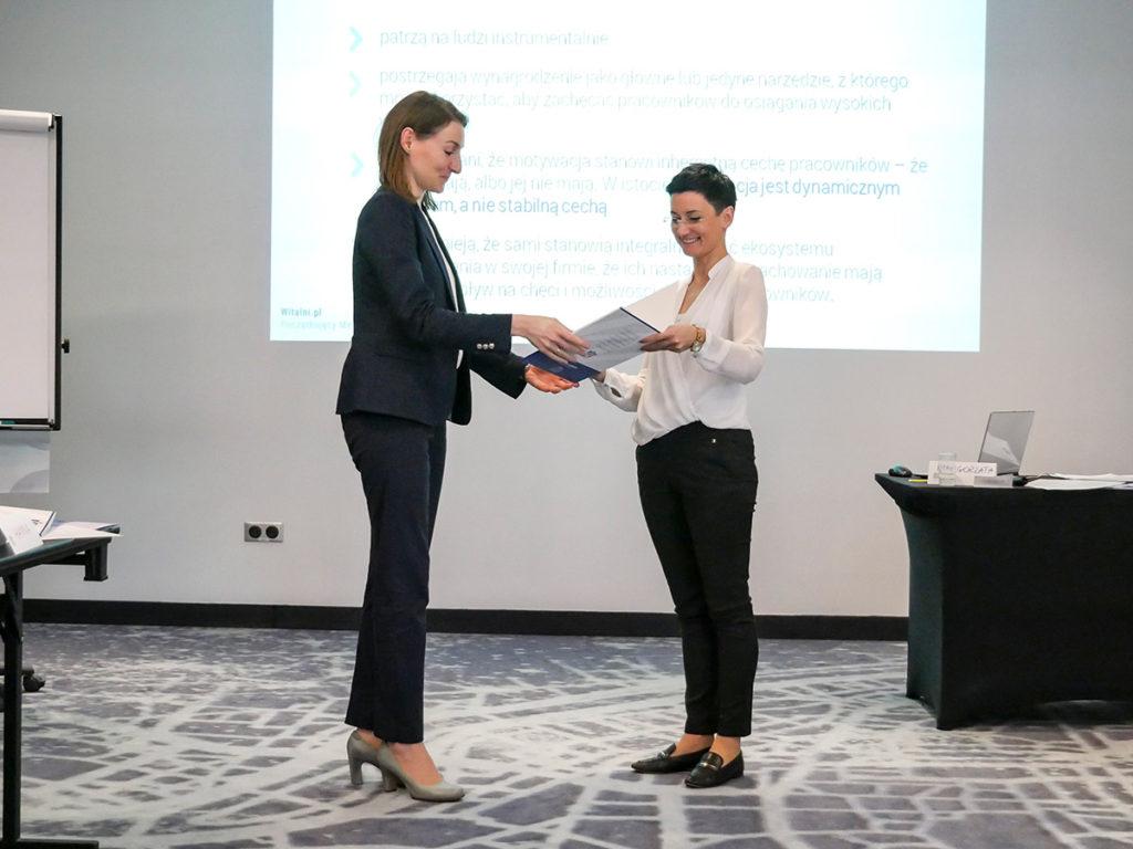Trener Małgorzata wręcza certyfikat ukończenia szkolenia