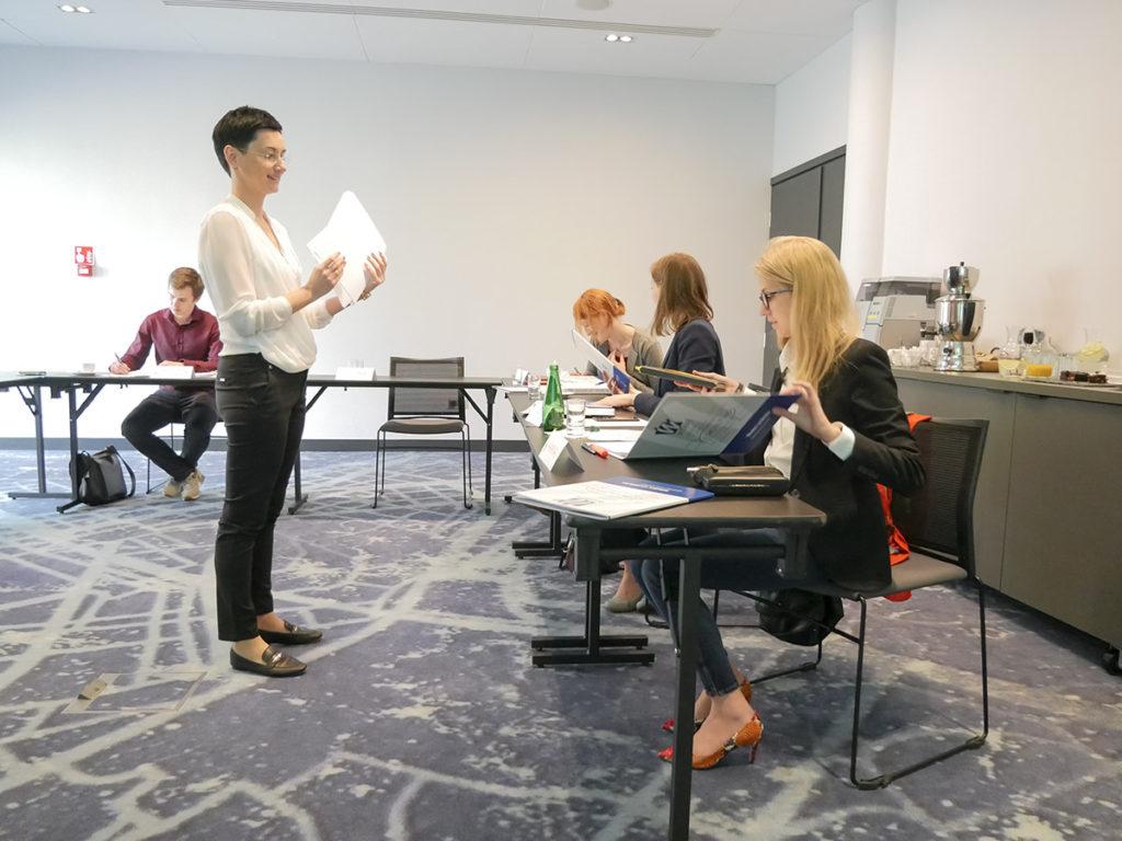 Trener Małgorzata rozdaje materiały uczestnikom szkolenia