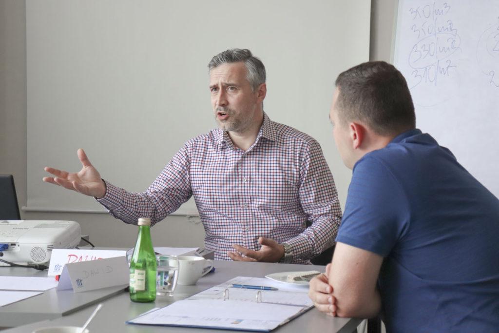 Trener Dawid rozmawia z uczestnikami o rolach, jakie zachodzą w negocjacjach handlowych
